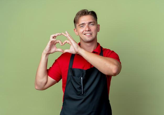Jonge zelfverzekerde blonde mannelijke kapper in uniform gebaren hart handteken geïsoleerd op olijfgroene ruimte met kopie ruimte