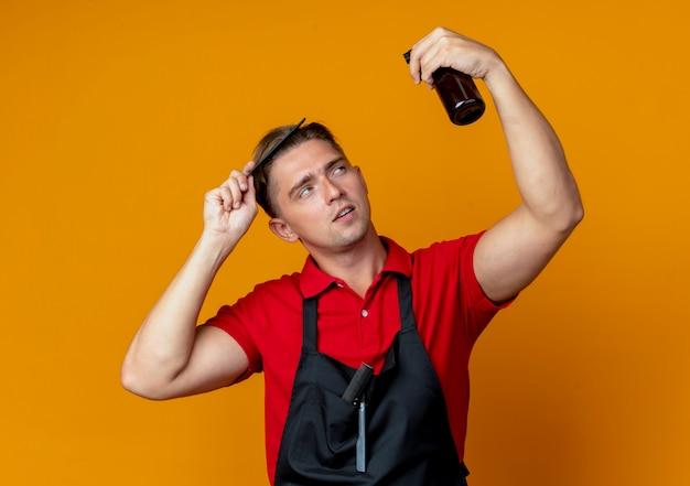 Jonge zelfverzekerde blonde mannelijke kapper in uniform haar kammen kijken spray fles geïsoleerd op oranje ruimte met kopie ruimte