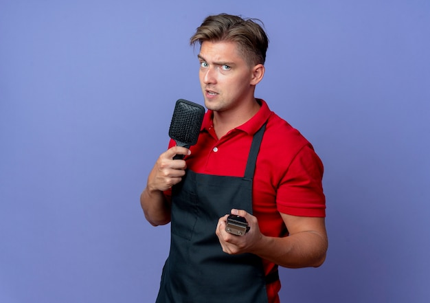 Jonge zelfverzekerde blonde mannelijke kapper in uniform houdt kam en haartrimmer geïsoleerd op violette ruimte met kopie ruimte