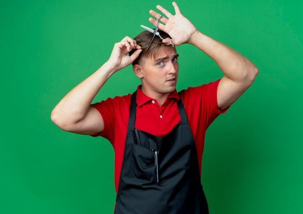 Jonge zelfverzekerde blonde mannelijke kapper in uniform knipt haar met een schaar geïsoleerd op groene ruimte met kopie ruimte