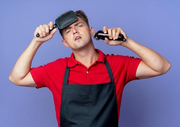Jonge zelfverzekerde blonde mannelijke kapper in uniform zet kam op voorhoofd met haartrimmer op violet met kopie ruimte