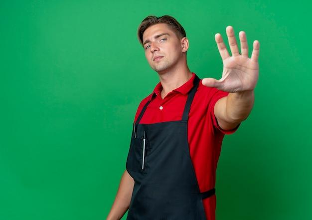 Jonge zelfverzekerde blonde mannelijke kapper in uniforme gebaren stop handteken geïsoleerd op groene ruimte met kopie ruimte