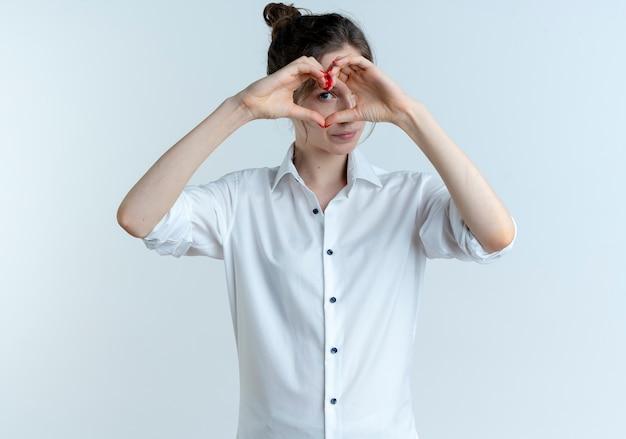 Jonge zelfverzekerde blonde russische meisje gebaren en kijkt door hart handteken geïsoleerd op een witte ruimte met kopie ruimte