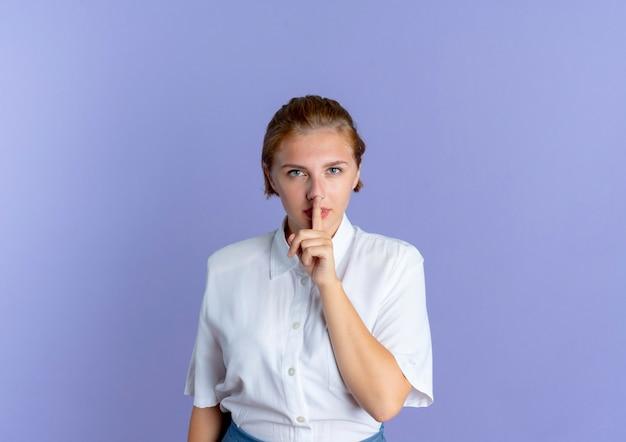 Jonge zelfverzekerde blonde russische meisje gebaren stilte stil geïsoleerd op paarse achtergrond met kopie ruimte