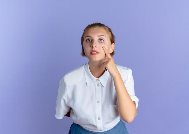 Jonge zelfverzekerde blonde russische meisje wijst naar oog geïsoleerd op paarse achtergrond met kopie ruimte