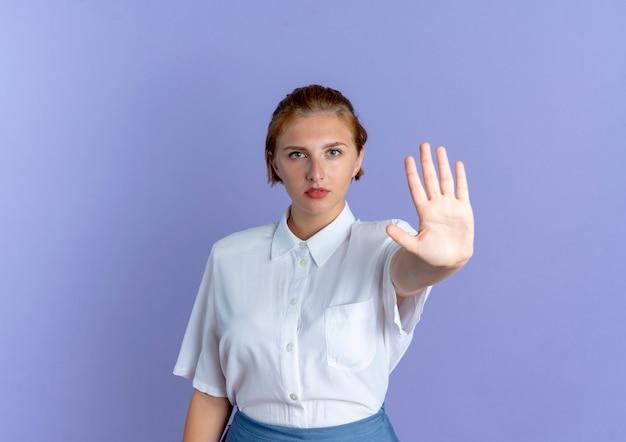 Jonge zelfverzekerde blonde russische meisjesgebaren stoppen handteken geïsoleerd op paarse achtergrond met kopie ruimte