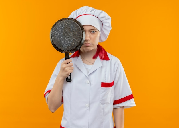 Jonge zelfverzekerde blonde vrouwelijke chef-kok in uniform chef-kok sluit oog met koekenpan geïsoleerd op oranje muur