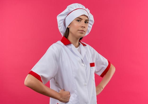 Jonge zelfverzekerde kaukasische kok meisje in uniform chef houdt vuisten op taille en kijkt naar camera geïsoleerd op roze ruimte met kopie ruimte