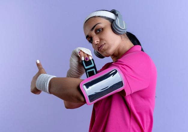 Jonge zelfverzekerde kaukasische sportieve vrouw met hoofdband en polsbandjes op koptelefoon corrigeert telefoon armband geïsoleerd op paarse achtergrond met kopie ruimte