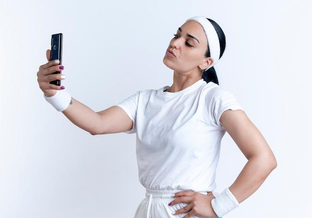 Jonge zelfverzekerde kaukasische sportieve vrouw met hoofdband en polsbandjes staat zijwaarts kijken naar telefoon neemt selfie geïsoleerd op witte ruimte met kopie ruimte