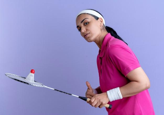 Jonge zelfverzekerde kaukasische sportieve vrouw met hoofdband en polsbandjes staat zijwaarts met shuttle op rackets geïsoleerd op paarse achtergrond met kopie ruimte