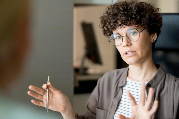 Jonge zelfverzekerde leraar of bedrijfsagent die cliënt raadpleegt tijdens vergadering of student tijdens individuele les