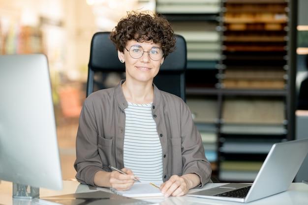Jonge zelfverzekerde leraar of officemanager die aantekeningen maakt door bureau terwijl hij op kantoor werkt