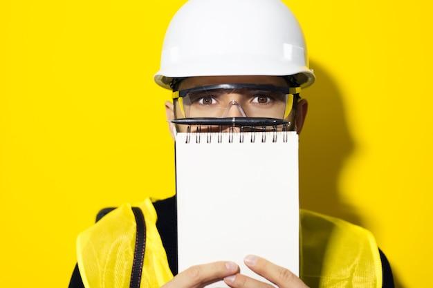 Jonge zelfverzekerde man, bouwer ingenieur schrijven in notitieblok, met behulp van draadloze oortelefoons, veiligheidshelm en bril dragen voor constructie op gele muur.