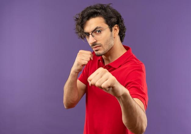 Jonge zelfverzekerde man in rood shirt met optische bril staat zijwaarts en met vuisten omhoog en klaar om te slaan geïsoleerd op violette muur