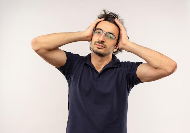 Jonge zelfverzekerde man in zwart shirt met optische bril houdt hoofd met handen en kijkt geïsoleerd op een witte muur