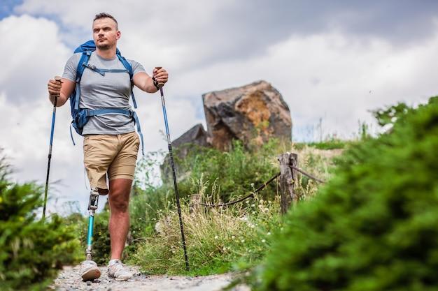 Jonge zelfverzekerde man met prothese die nordic walking probeert terwijl hij buiten tijd doorbrengt