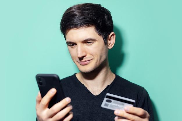 Jonge zelfverzekerde man met smartphone en creditcard in de hand op muur van aqua menthe kleur.