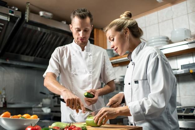 Jonge zelfverzekerde professionele chef-kok met mes en komkommer die zijn vrouwelijke stagiair raadpleegt die verse courgette snijdt terwijl hij hem helpt met koken