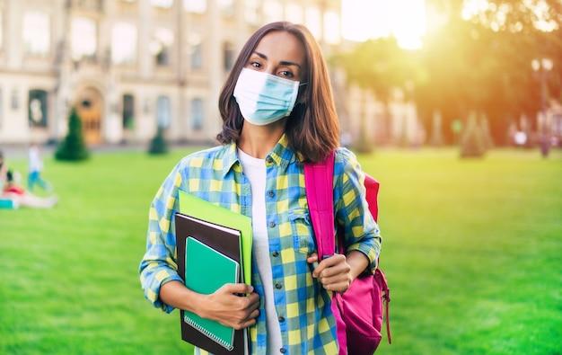 Jonge zelfverzekerde studentenvrouw in bescherming van het medische masker met boeken en documenten in handen en staande op de universiteitscampus
