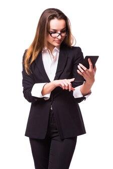 Jonge, zelfverzekerde, succesvolle en mooie bedrijfsvrouw met de tabletcomputer die op witte muur wordt geïsoleerd