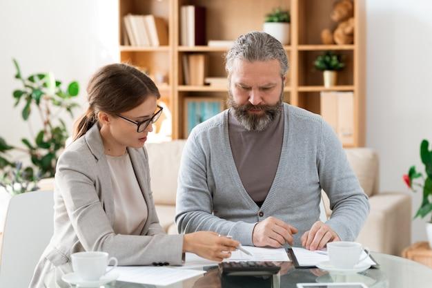 Jonge zelfverzekerde verzekeringsagent wijzend op papier terwijl de gepensioneerde man punten van het contract uitleggen
