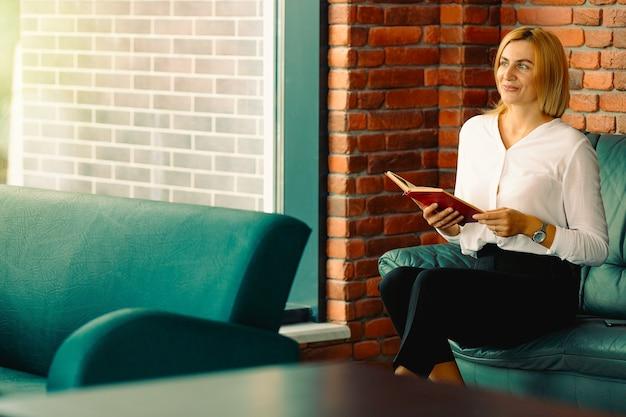 Jonge zelfverzekerde vrouw ondernemer geniet van de werkpauze zittend op een leren bank in kantoor interieur, intelligente geweldige vrouwelijke advocaat in formele slijtage een boek lezen.