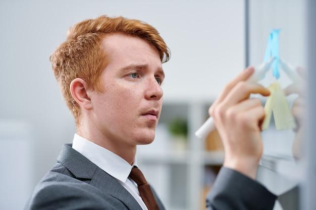 Jonge zelfverzekerde zaken- of financiële expert die tijdens het lezen op de notitie aan boord wijst