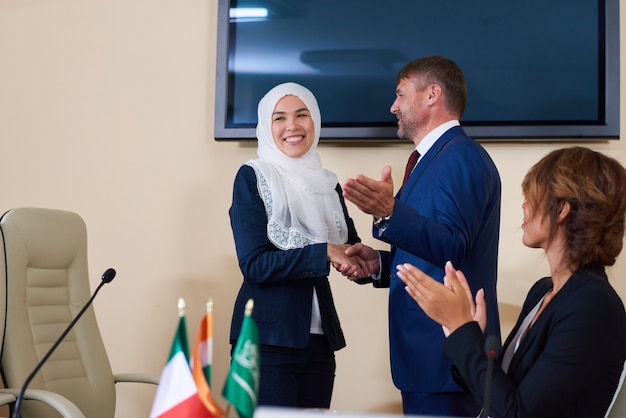 Jonge zelfverzekerde zakenman hand schudden van succesvolle vrouwelijke spreker in hijab na haar rapport op forum
