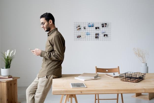 Jonge zelfverzekerde zakenman in vrijetijdskleding scrollen in smartphone of sms'en tijdens pauze in kantoor