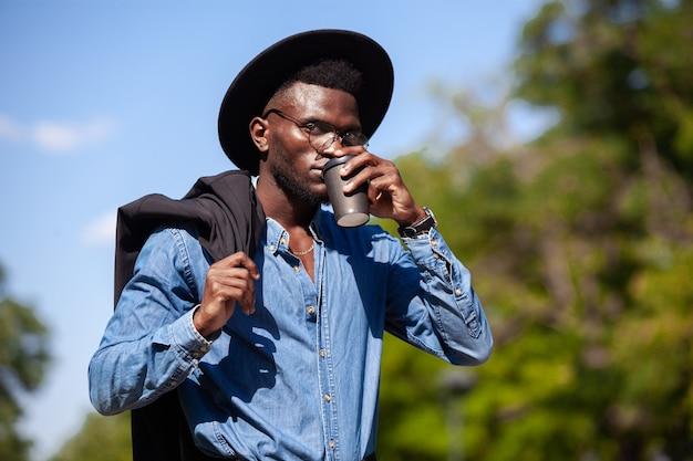 Jonge zelfverzekerde zwarte man in een hoed wandelen in een zomerpark