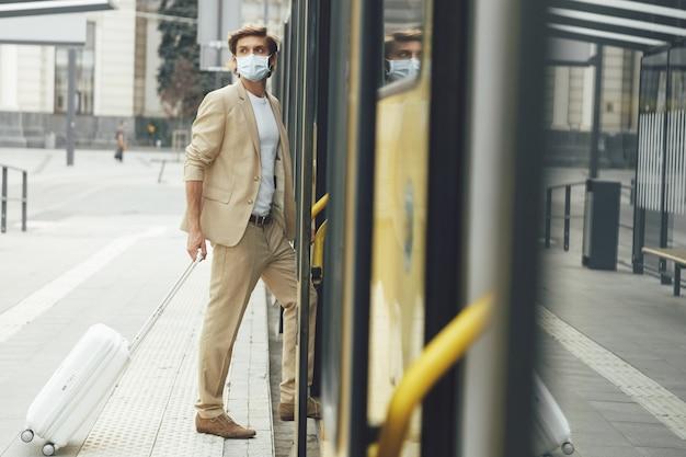 Jonge zelfvoorzienende man in pak en medisch masker staande in de buurt van gele tram bij halte