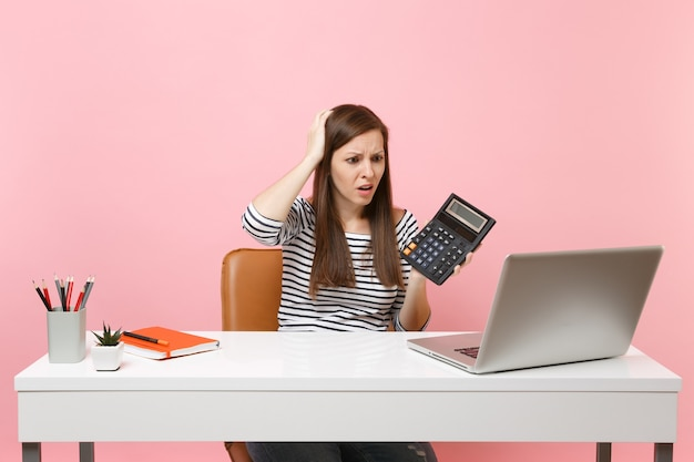 Jonge, zenuwachtige vrouw die zich vastklampt aan het hoofd met rekenmachine zit, werkt aan een project op kantoor met een moderne pc-laptop