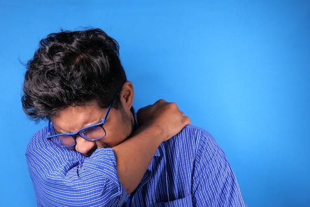 Jonge zieke man die haar neus en mond bedekt met arm.