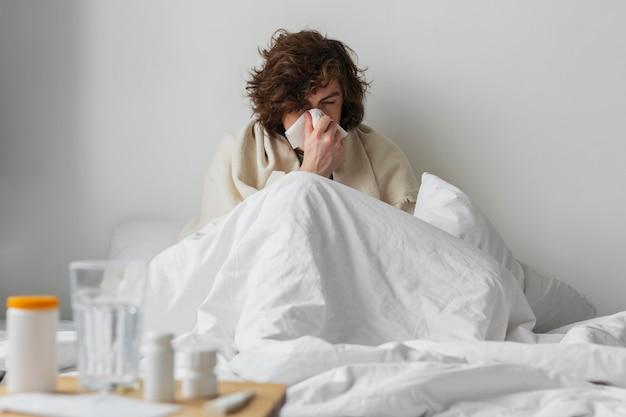 Jonge zieke man die in zijn bed blijft