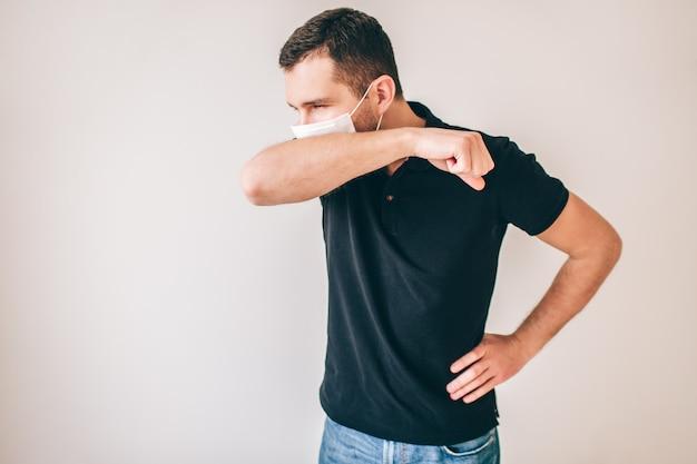Jonge zieke man geïsoleerd over muur. mannelijke persoon in zwart shirt hoesten door middel van medische bescherming masker. bedek de mond met de hand.