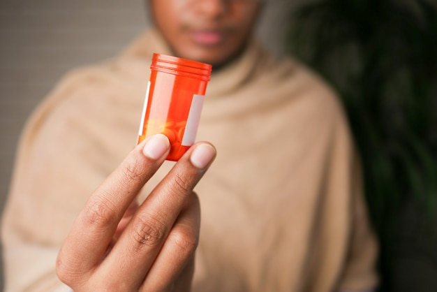 Jonge zieke man hand met medicijn pil container