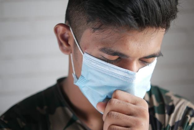 Jonge zieke man hoest en niest