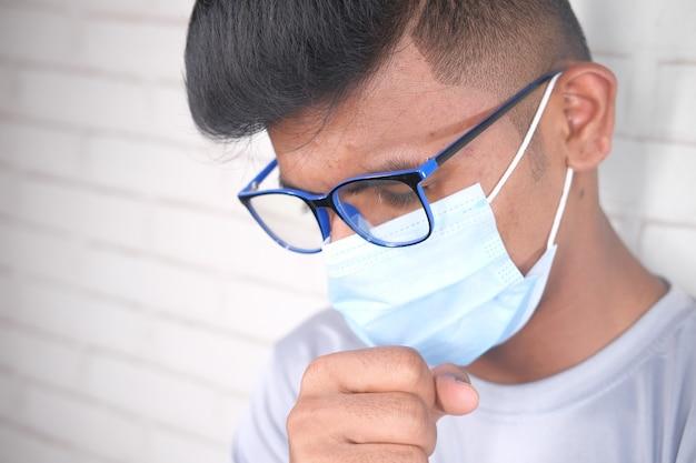 Jonge zieke man hoesten en niezen