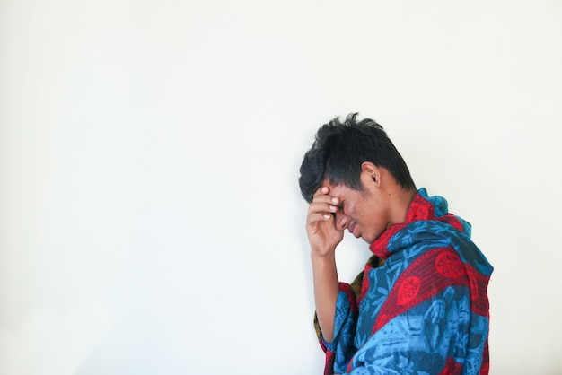 Jonge zieke man hoesten tegen witte muur
