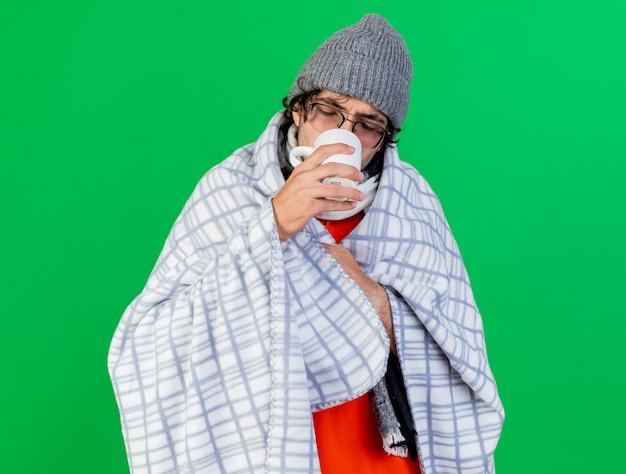 Jonge zieke man met bril, muts en sjaal gewikkeld in plaid grijpen geruite kopje thee drinken op zoek in beker geïsoleerd op groene muur
