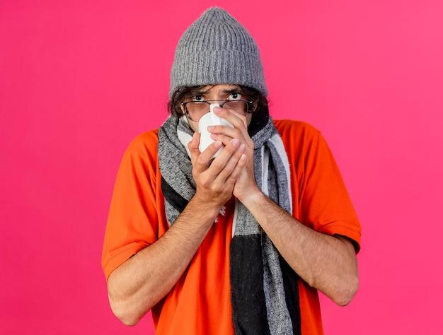 Jonge zieke man met bril, muts en sjaal kijken naar de voorkant drinken kopje thee geïsoleerd op roze muur