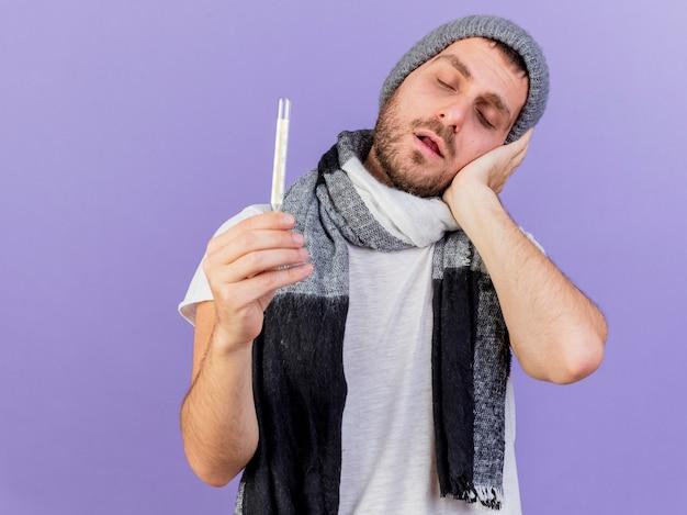 Jonge zieke man met muts met sjaal bedrijf thermometer en hand op wang geïsoleerd op paars te zetten