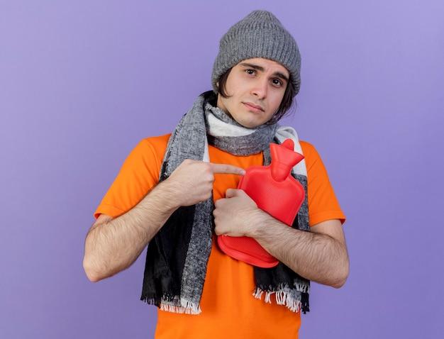 Jonge zieke man met muts met sjaal geknuffeld en wijst op warm waterzak geïsoleerd op paars