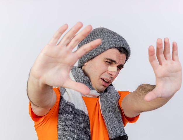 Jonge zieke man met winter hoed met sjaal hand in hand op camera met gips op mond geïsoleerd op wit