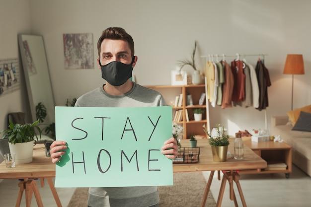 Jonge zieke man met zwart masker op gezicht met papieren poster met de aanbeveling om thuis te blijven terwijl je het aan je laat zien