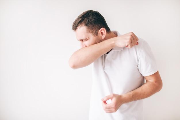 Jonge zieke mens die over witte muur wordt geïsoleerd. hoest hardop en bedek de mond met een elleboog. pijnlijke hoest.