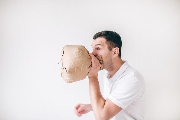 Jonge zieke mens die over witte muur wordt geïsoleerd. man braakt in tas. lijdt aan slechte astma of spijsvertering.