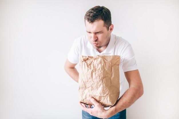 Jonge zieke mens die over witte muur wordt geïsoleerd. man braken in de tas. slechte spijsvertering en buikpijn.