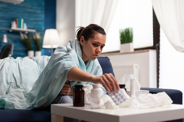 Jonge zieke volwassene die thuis medicijnen tegen griep neemt